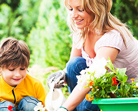Mother Planting Flowers with Son